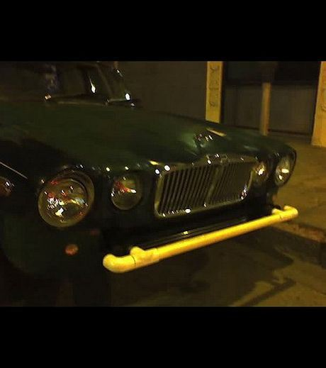 A yellow iron bar acting as a car bumper