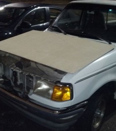 A cardboard has been used as a car hood (car bonnet)