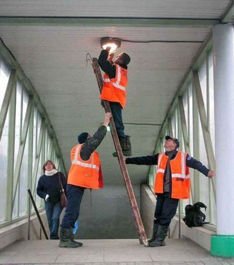 These electricians hold the ladder to keep their colleague from falling