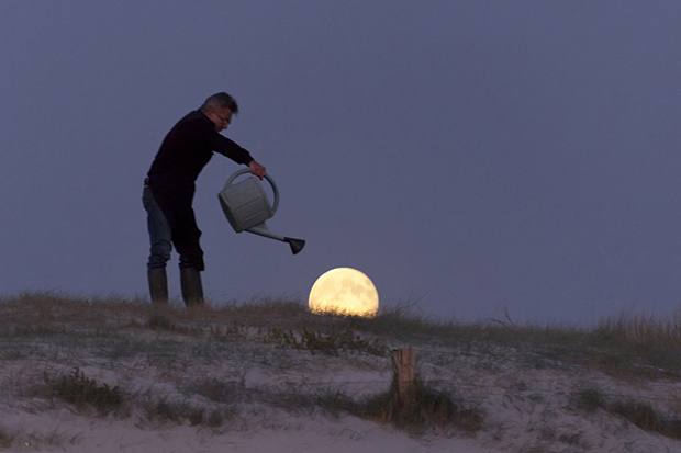 Seems as man is pouring watering over the moon.