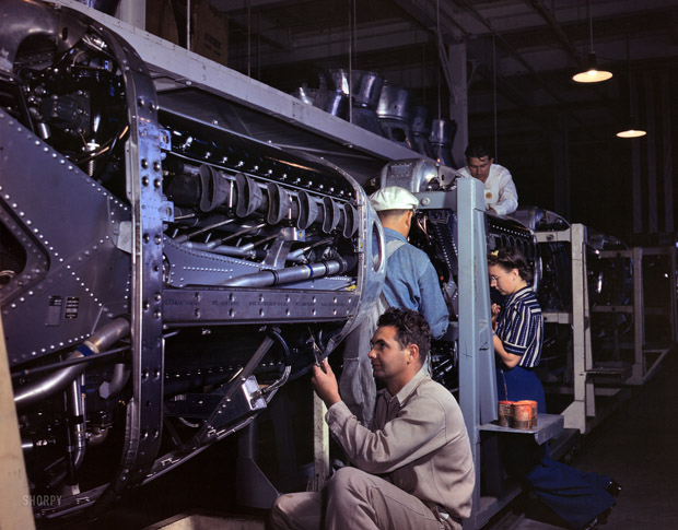 October 1942. Inglewood, California. Employees of the North American Aviation assemble the cover of an Allison engine for a P-51 Mustang fighter plane.