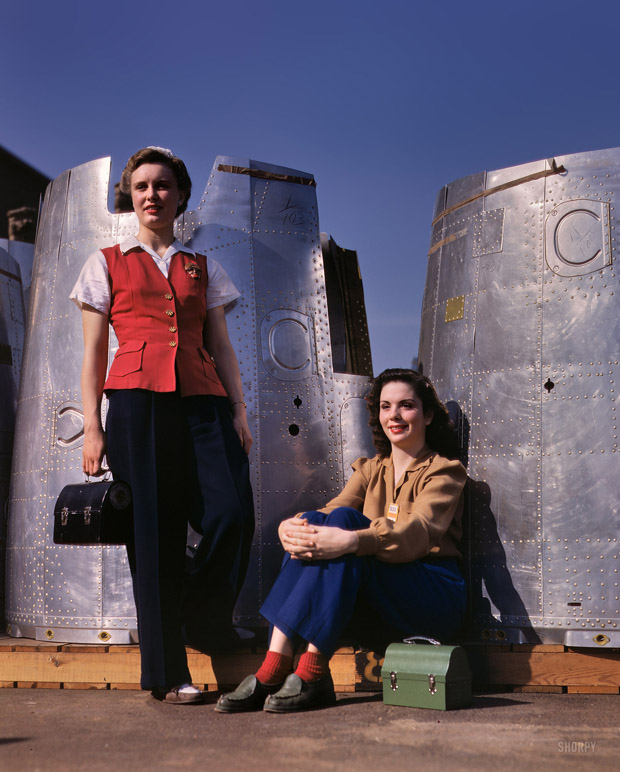 October 1942. Two workers of the assembly line in Long Beach, California. In the background are two parts of a heavy bomber.