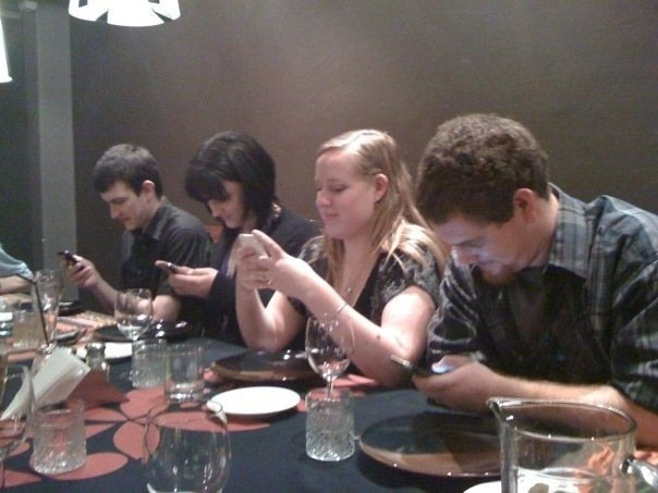 Friends discussing love and life on dinner but busy on mobile phone