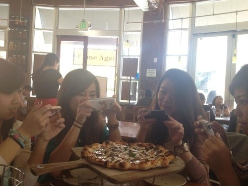 Friends enjoy delicious pizza using mobile phone