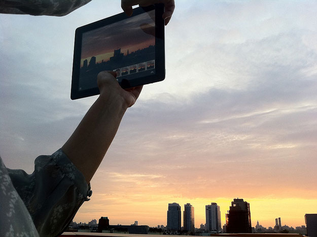 Man watching sun set on tablet screen