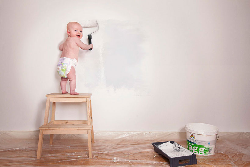 baby painting wall with a roller