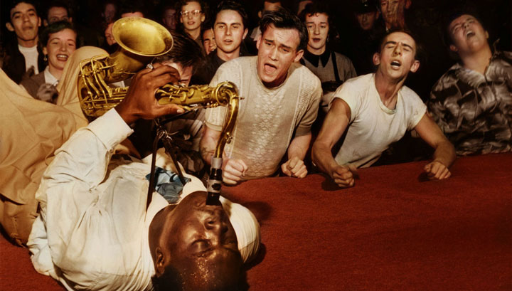 colorized photo of Big Jay McNeely in full frenzy of crowd at Olympic Auditorium, Los Angeles, 1953
