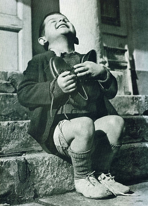 25. An Austrian boy receives new shoes during the Second World War