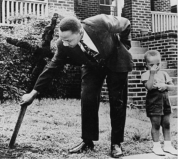 Martin Luther King and his son removes a burned cross from their yard in 1960