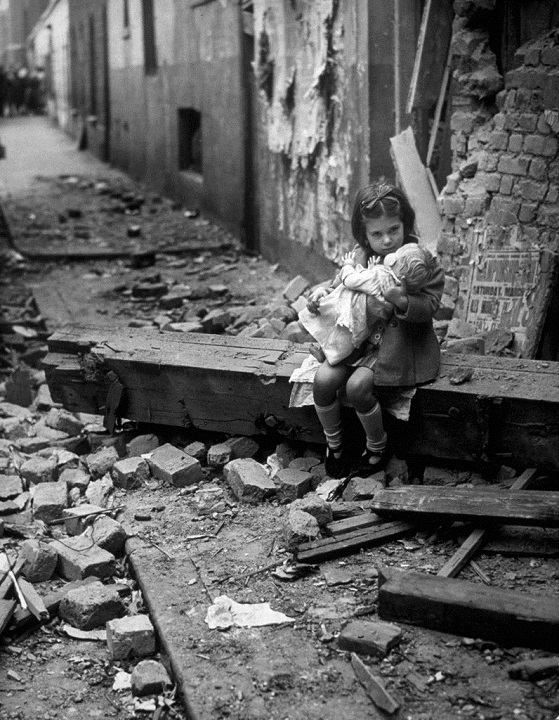 14. A little girl with her doll sitting on the ruins of her bombed house in London in 1940
