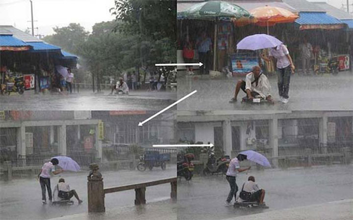 This woman who helps a disabled person during a rain-Emotional Charged Photographs That Prove That Humanity Is Not Yet Lost-12