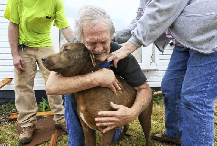 This man who hugs his dog after  the dog found him under the rubble of his house blown by a tornado -Emotional Charged Photographs That Prove That Humanity Is Not Yet Lost-17