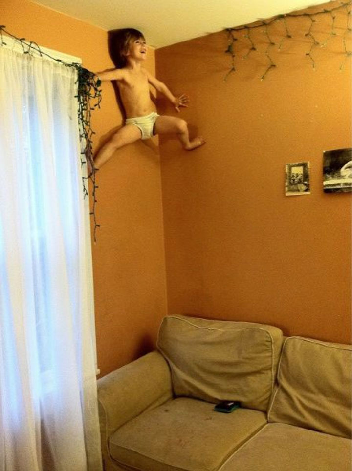 This little boy perched on the ceiling as Spider-Man-Children Who Use Their Imagination To Do Weird And Hilarious Things-6