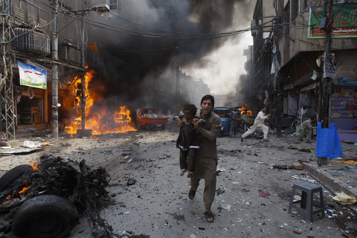 A man carries a child away from the site of a bomb attack in Pakistan-Most Touching Photographs-20