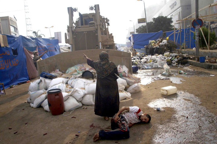 A woman keeps a military bulldozer from rolling over an injured man in Cairo, Egypt-Most Touching Photographs-21