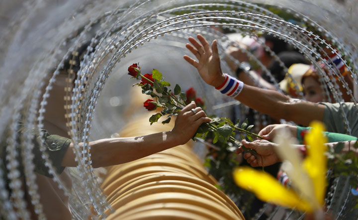 An anti-government protest offers a rose to a soldier in Bangkok-Most Touching Photographs-22