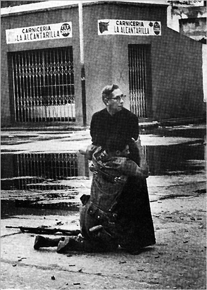 26. The priest Luis Padillo made a final prayer for a man wounded by gunfire from a sniper fire in Venezuela-Most Touching Photographs-29