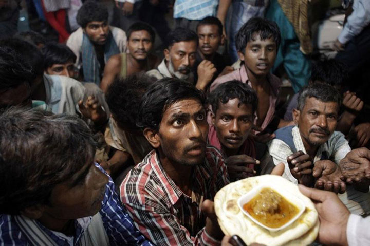 Homeless waiting to receive free food outside a mosque in New Delhi, India-Most Touching Photographs-8