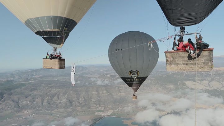 Amazing Stunt Of Walking On A Tightrope Between Two Air Balloons Above Clouds-6