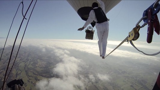 Amazing Stunt Of Walking On A Tightrope Between Two Air Balloons Above Clouds-
