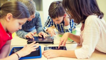 Elementary students having fun playing online games on tablets Feature Image